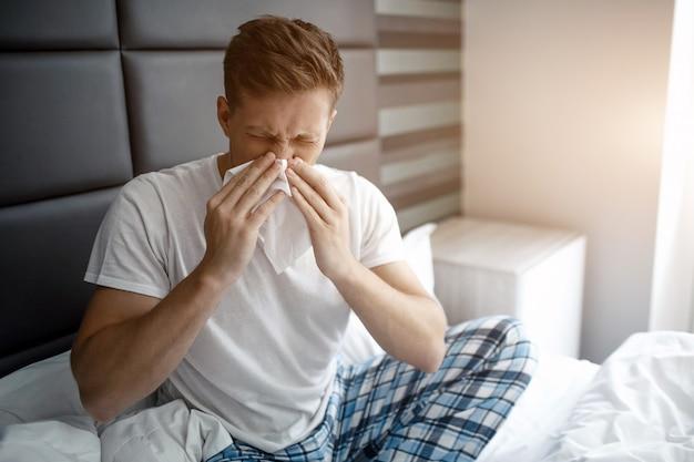 Jonge man zit op bed vroeg in de ochtend. hij niest in een wit servet. zieke en zieke jongeman.