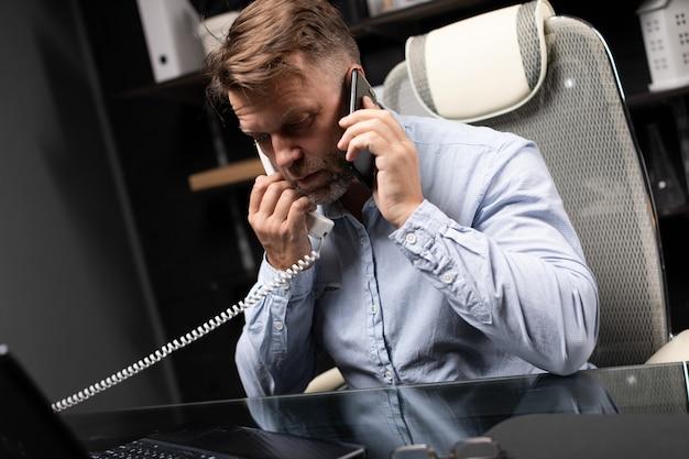 Jonge man zit op computer bureau en vast toestel en mobiele telefoon te houden