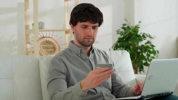 Jonge man zit op de bank in de woonkamer, maakt online aankopen via een laptop, houdt een creditcard vast, betaalt voor aankopen in een online winkel die thuis rust