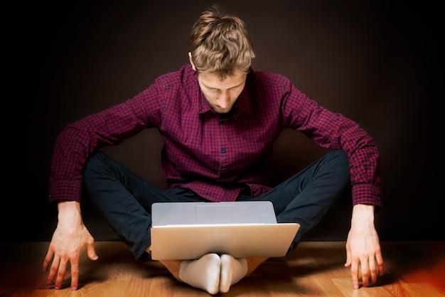 Jonge man zit op de vloer en gebruikt een laptop op een donkere achtergrond b