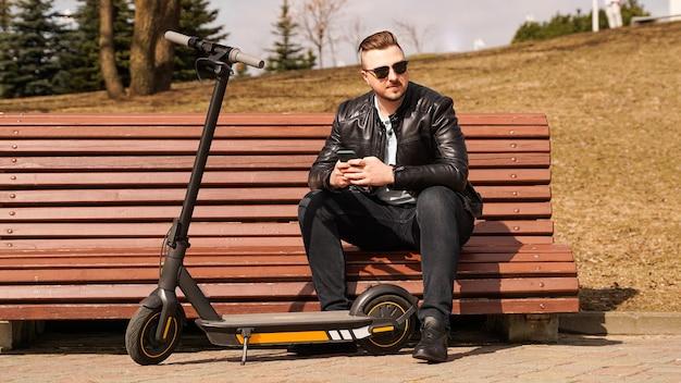 Jonge man zit op een bankje op een elektrische scooter van de lentedag naast een bankje
