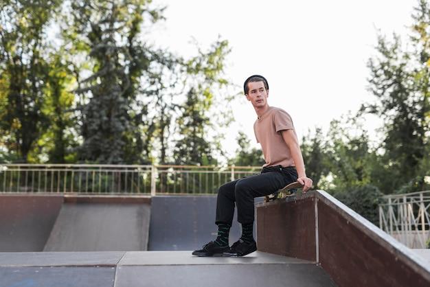 Jonge man zit op een skateboard