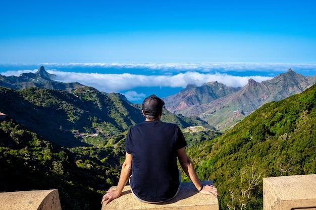 Jonge man zit te kijken naar het anaga-gebergte in het noorden van tenerife in spanje