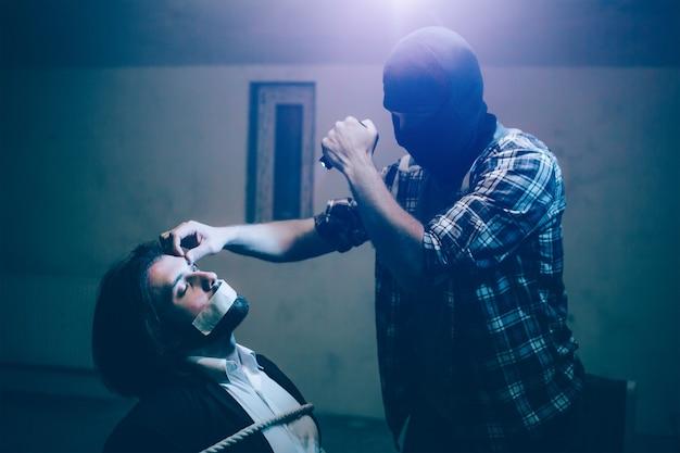 Jonge man zit vastgebonden aan een stoel en houdt de ogen gesloten