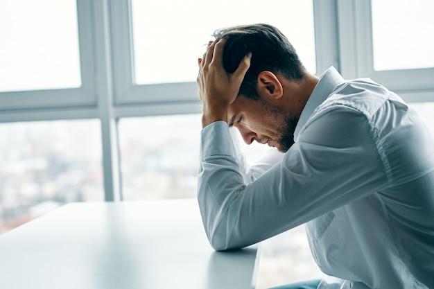 Jonge man zittend aan een tafel depressief tegen het raam