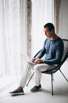 Jonge man zittend in een stoel en met behulp van laptop