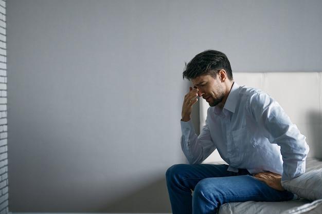 Jonge man zittend op bed depressief