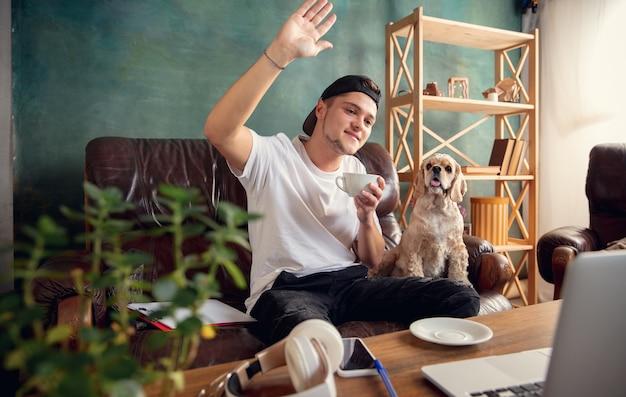 Jonge man zittend op de bank thuis met schattige hond en online chatten met zijn vrienden.