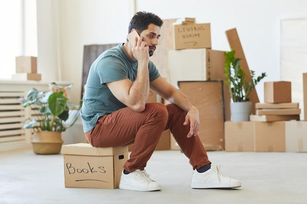 Jonge man zittend op de doos en praten over de mobiele telefoon, hij bestelt de auto voor verhuizing