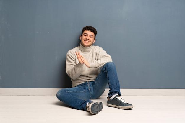Jonge man zittend op de vloer applaudisseren na de presentatie in een conferentie