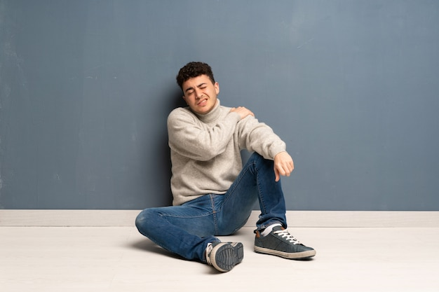 Jonge man zittend op de vloer die lijden aan pijn in de schouder voor het hebben gedaan van een inspanning