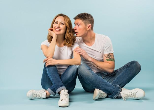 Jonge man zittend op de vloer fluisteren in het oor van vriendin tegen blauwe achtergrond