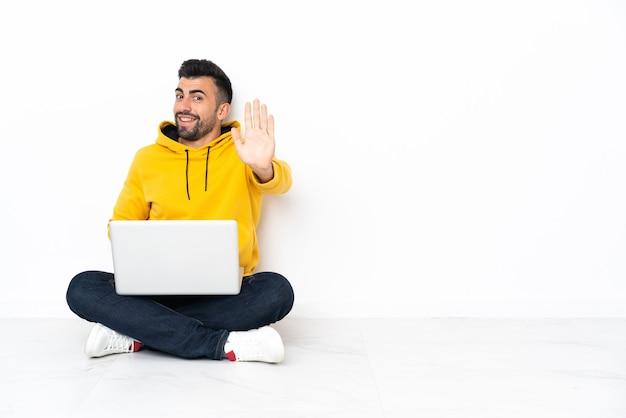 Jonge man zittend op de vloer met zijn laptop groeten met hand met gelukkige uitdrukking