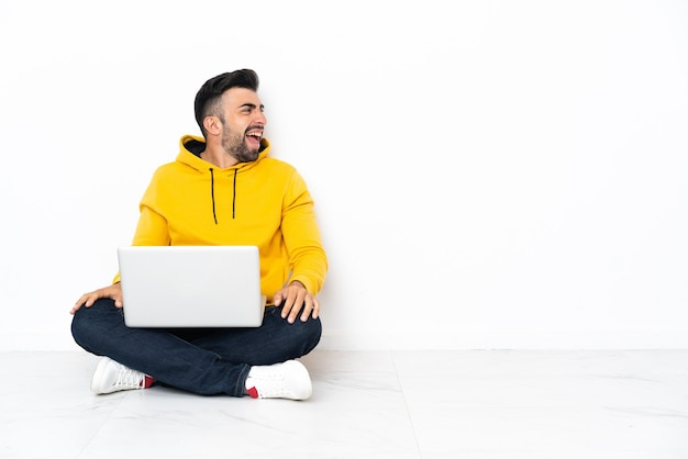 Jonge man zittend op de vloer met zijn laptop lachen in laterale positie