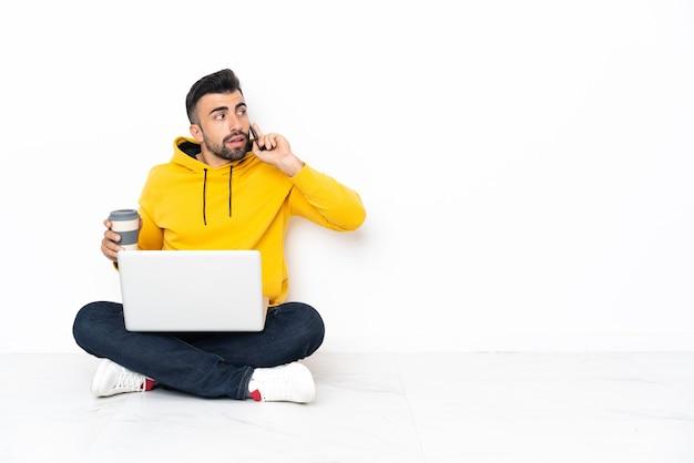 Jonge man zittend op de vloer met zijn laptop met koffie om mee te nemen en een mobiel