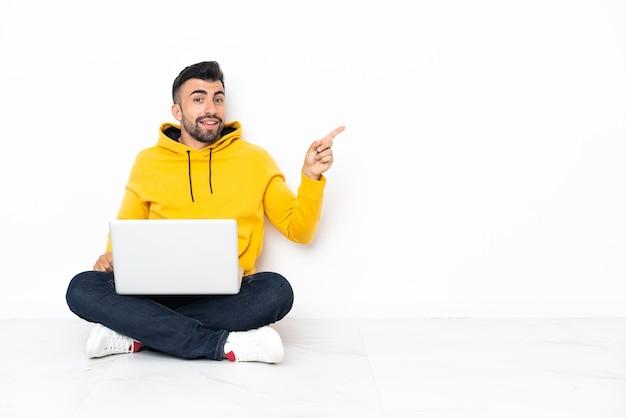 Jonge man zittend op de vloer met zijn laptop wijzende vinger naar de zijkant