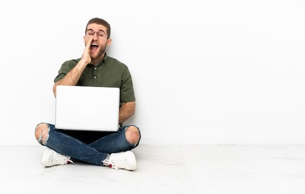 Jonge man zittend op de vloer schreeuwend met mond wijd open