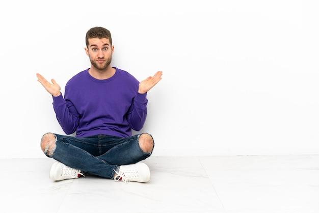 Jonge man zittend op de vloer twijfelend terwijl hij zijn handen opsteekt