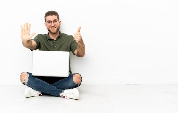 Jonge man zittend op de vloer zes tellen met vingers