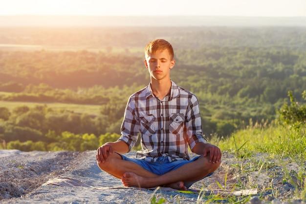 Jonge man zittend op de weg in de positie van lotus op een zonnige dag