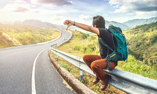 Jonge man zittend op de weg. reis- en vakantieconcepten. backpacker op de weg. reizen man liften