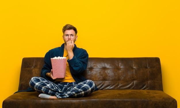 Jonge man zittend op een bank met popcorns. bioscoop concept