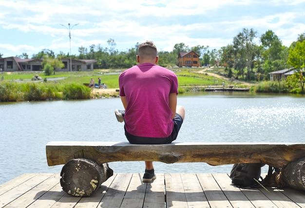 Jonge man zittend op een bankje tegen het meer