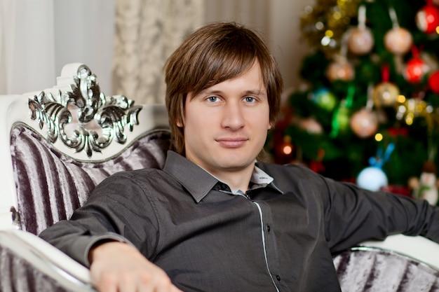 Jonge man zittend op een leunstoel