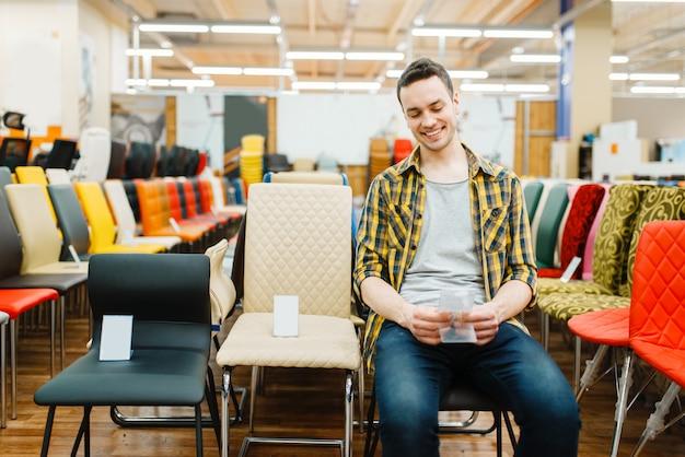 Jonge man zittend op een stoel in de showroom van de meubelwinkel.
