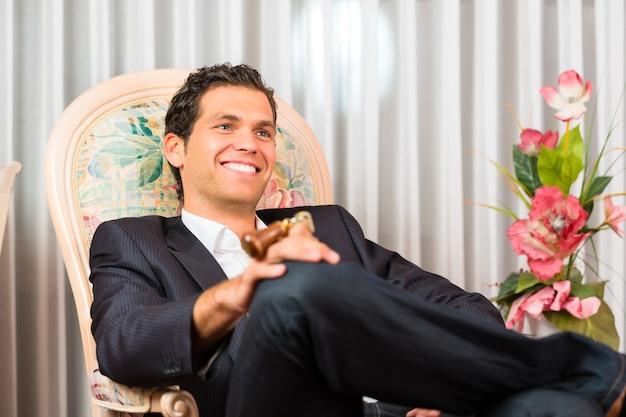 Jonge man zittend op een stoel in een hotelkamer