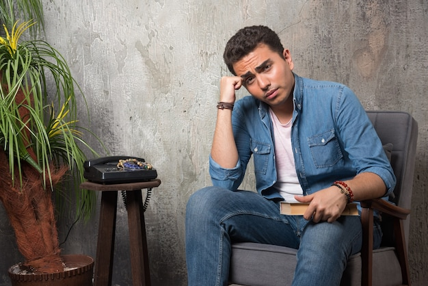 Jonge man zittend op een stoel met boek over marmeren achtergrond. hoge kwaliteit foto