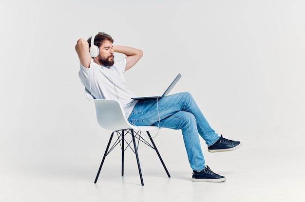 Jonge man zittend op een stoel met een laptop in koptelefoon entertainment