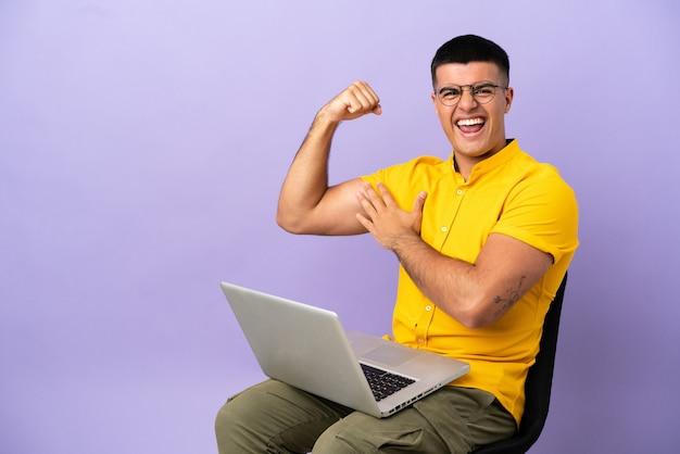 Jonge man zittend op een stoel met laptop die een sterk gebaar doet
