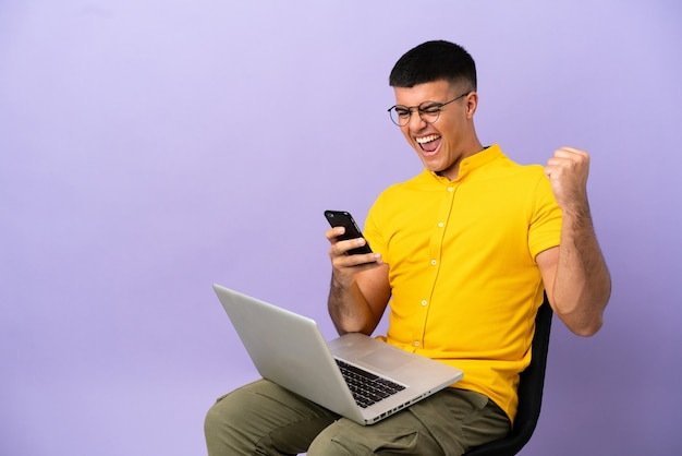 Jonge man zittend op een stoel met laptop met telefoon in overwinningspositie