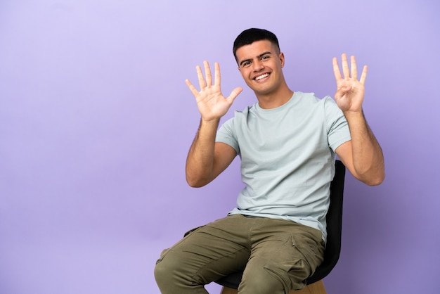 Jonge man zittend op een stoel over geïsoleerde achtergrond telt negen met vingers