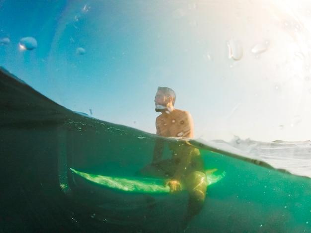 Jonge man zittend op een surfplank in de blauwe zee
