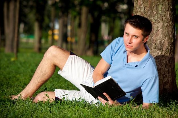 Jonge man zittend op groen gras en leesboek