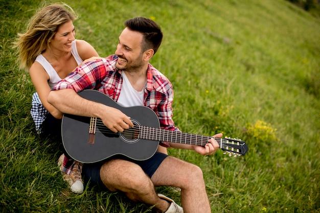 Jonge man zittend op het gras met zijn vriendin en gitaar spelen