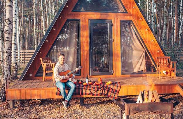 Jonge man zittend op het terras van zijn huis in de herfst