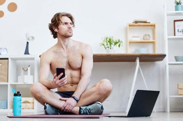 Jonge man zittend op oefeningsmat voor laptop en rusten