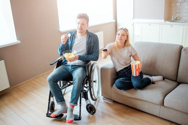 Jonge man zittend op rolstoel en kijken naar film met vriendin. man met een handicap en speciale behoeften. de jonge vrouw zit op bank en houdt kom met voedsel. afstandsbediening.