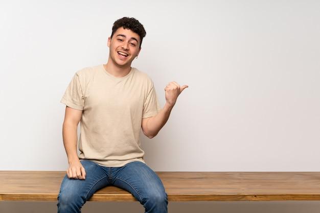 Jonge man zittend op tafel wijst naar de zijkant om een product te presenteren