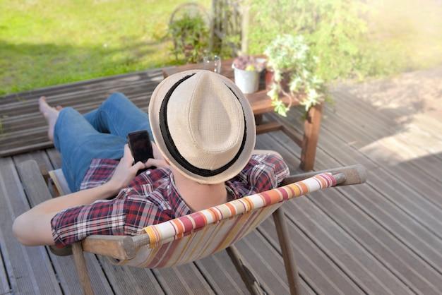 Jonge man zittend op terras in de tuin en met behulp van zijn mobiele telefoon