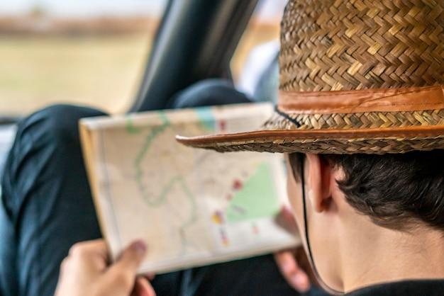 Jonge man zoekt de weg met behulp van een kaart zittend in de auto