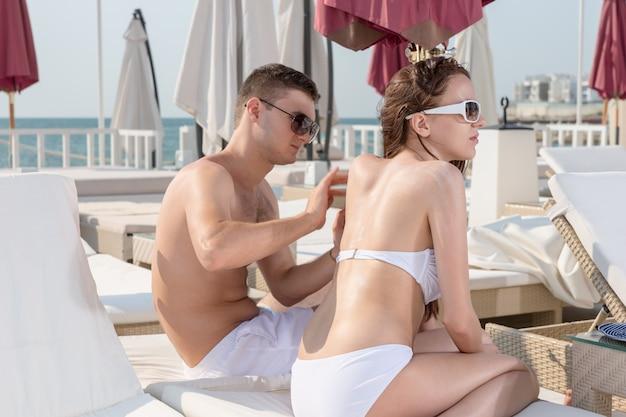 Jonge man zonnebrand lotion op de achterkant van de jonge vrouw wrijven terwijl u samen ontspant op de loungestoel op het zonnige dek van het luxe vakantieresort aan het strand