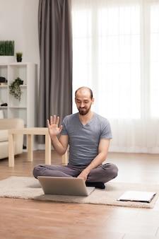 Jonge man zwaaien op videoconferentie tijdens zelfisolatie.