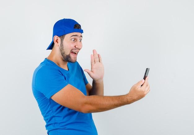 Jonge man zwaaiende hand op videochat in blauw t-shirt en pet en op zoek vrolijk