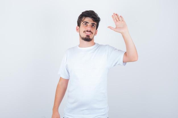 Jonge man zwaait met de hand om afscheid te nemen in t-shirt en ziet er schattig uit
