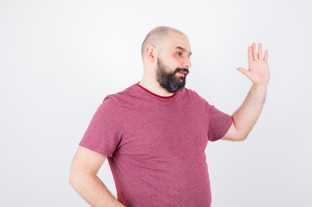 Jonge man zwaait met de hand voor begroeting in roze t-shirt en ziet er helder uit, vooraanzicht.
