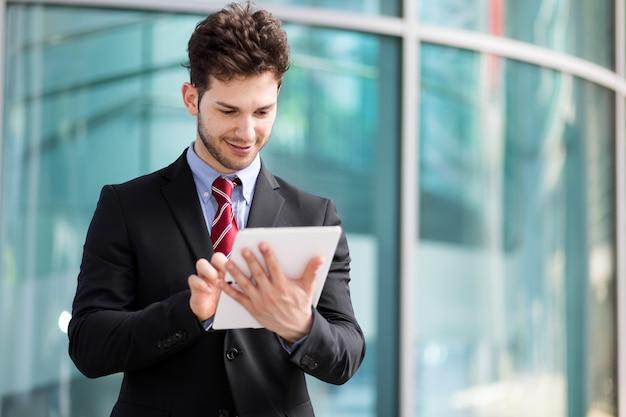 Jonge manager die een digitale tablet in openlucht gebruikt